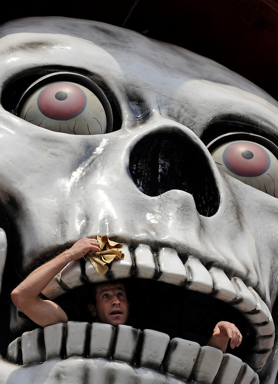 Description of . A man cleans the giant skull of a ghost train at the opening of the 575. Cranger Fair in Herne, western Germany, Friday, Aug. 6, 2010. What once started as a horse market in the 15th century has become one of Germany's biggest fun fairs with 500 exhibitors and about four million visitors within ten days. (AP Photo/Martin Meissner)