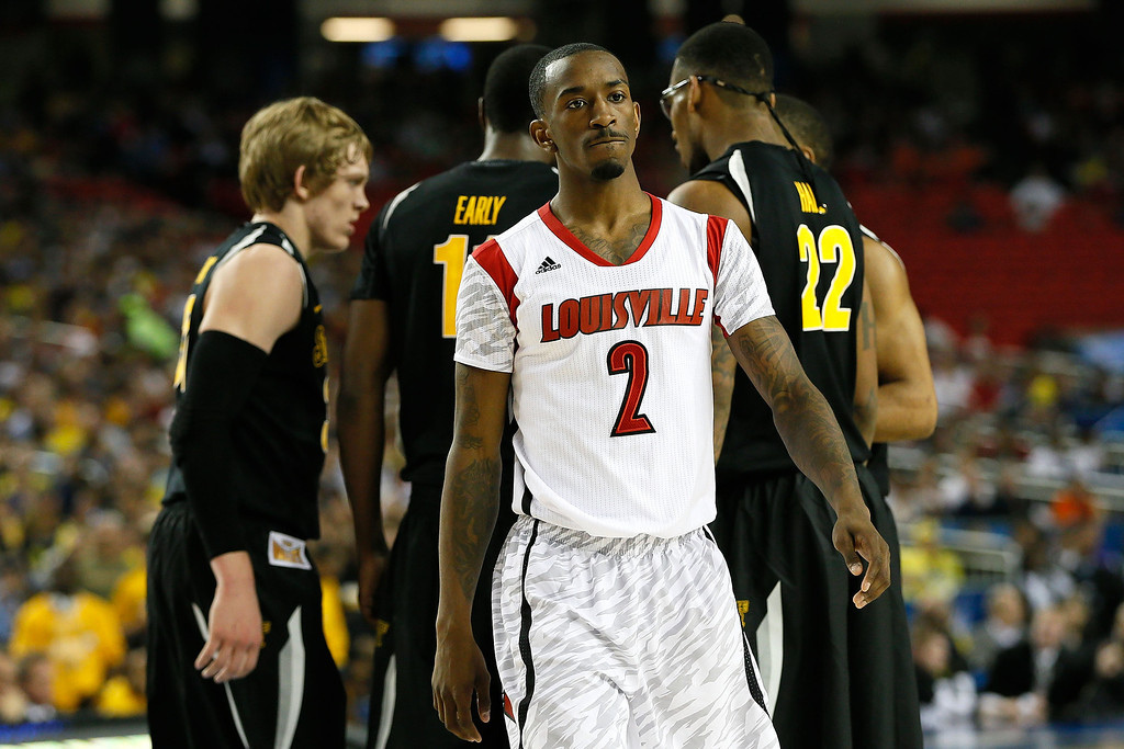 Description of . ATLANTA, GA - APRIL 06:  Russ Smith #2 of the Louisville Cardinals reacts in the first half as the Wichita State Shockers huddle during the 2013 NCAA Men's Final Four Semifinal at the Georgia Dome on April 6, 2013 in Atlanta, Georgia.  (Photo by Kevin C. Cox/Getty Images)