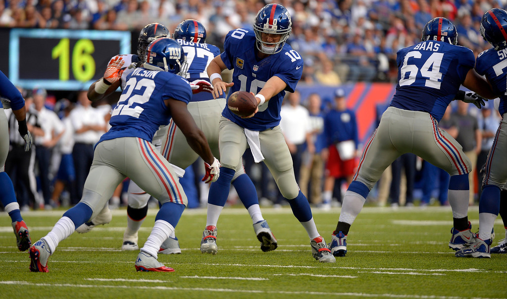 Description of . Quarterback Eli Manning (10) of the New York Giants fakes the handoff to running back David Wilson (22) of the New York Giants against the Denver Broncos in the first quarter September 15, 2013 MetLIFE Stadium. (Photo by John Leyba/The Denver Post)