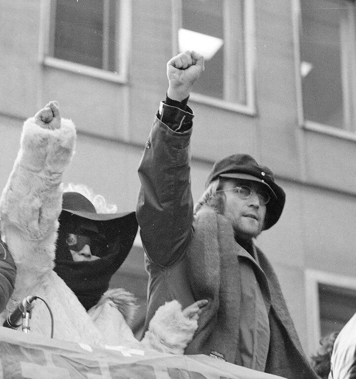 Description of . John Lennon and his wife Yoko Ono raise their fists as they join a protest  in front of British Overseas Airways Corp. offices in New York in this Feb. 5, 1972, file photo.  The demonstrators called for the withdrawal of British troops from Northern Ireland.The FBI has released its final surveillance documents on Lennon to a university historian who has waged a 25-year legal battle to obtain the secret files. The 10 pages contain new details about Lennon's ties to leftist and anti-war groups in London in the early 1970s, but nothing indicating government officials considered the former Beatle a serious threat, historian Jon Wiener told the Los Angeles Times in Wednesday's editions,Dec. 20, 2006.   (AP Photo/Ron Frehm, file)