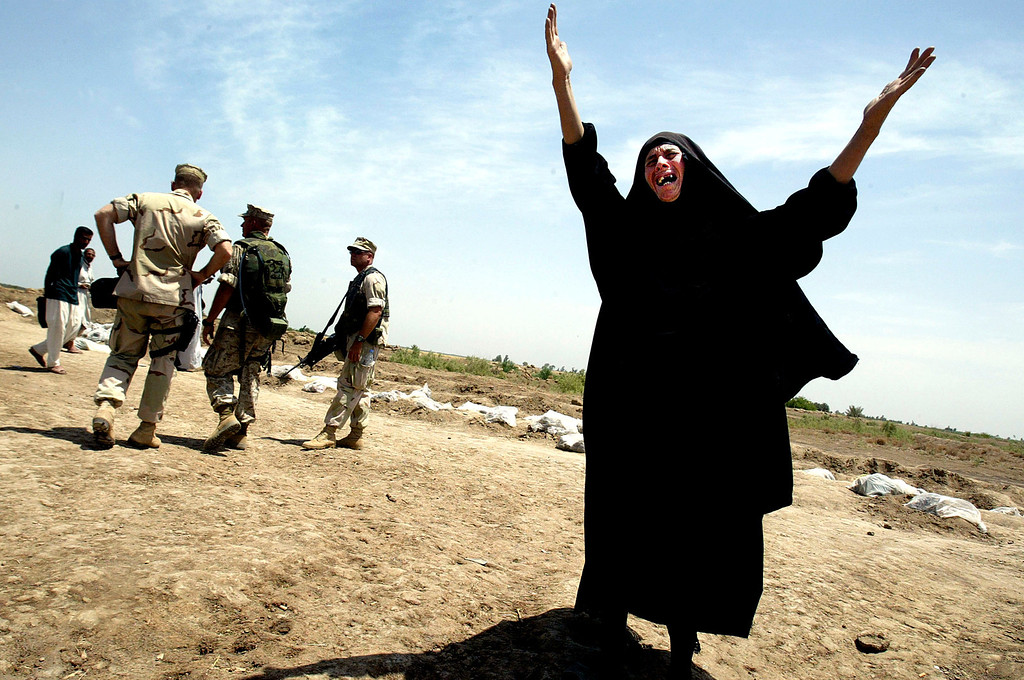Description of . A woman cries out the name of her missing son as U.S. Marines searched for evidence at a mass grave on May 14, 2003 in Hillah, Iraq. At least 2,000 bodies had been dug out at the site making it the largest mass grave discovered in Iraq following the fall of Saddam Hussein\'s regime. (Photo by Mario Tama/Getty Images)
