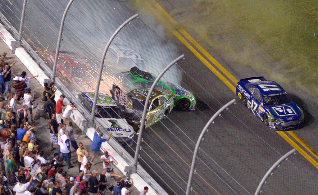 Description of . Danica Patrick (10), David Gilliland (38), Ricky Stenhouse Jr. (17), Kyle Busch (18), J J Yeley (36) and Casey Mears (13) slide along the wall of the front stretch after colliding on the final lap during the NASCAR Sprint Cup auto race at Daytona International Speedway in Daytona Beach, Fla., Saturday, July 6, 2013. (AP Photo/Phelan M. Ebenhack)