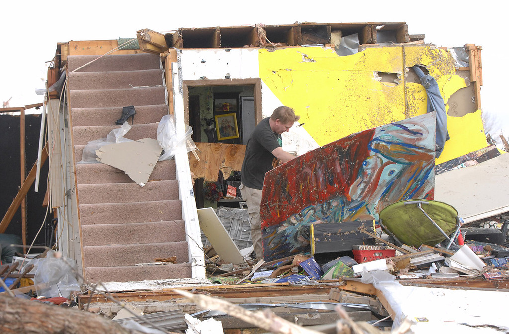 Description of . A Washington homeowner moves debris next to a set of stairs that once lead to the second floor of his home in Washington, Ill., Sunday, Nov. 17, 2013. Intense thunderstorms and tornadoes swept across the Midwest, causing extensive damage in several central Illinois communities while sending people to their basements for shelter. (AP Photo/The Pantagraph, Steve Smedley)