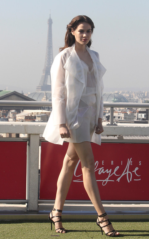 Description of . A model presents a creation as part of French fashion designer Christine Phung's ready-to-wear Spring/Summer 2014 fashion collection presented in Paris, Tuesday, Sept.24, 2013. The Eiffel Tower is seen in background. (AP Photo/Thibault Camus)