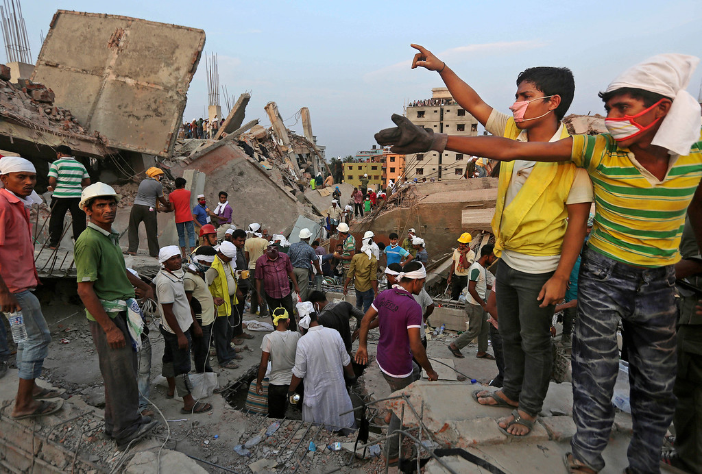 Description of . Bangladeshi rescuers from a youth group gesture for help at the site of a building that collapsed Wednesday in Savar, near Dhaka, Bangladesh, Thursday, April 25, 2013. (AP Photo/Kevin Frayer)