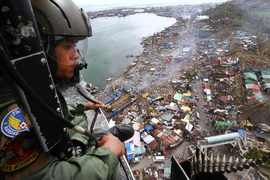 Description of . A Philippine Air Force crew looks out from his helicopter as Typhoon Haiyan-ravaged city of Tacloban is seen in the background, during a flight to deliver relief goods in Leyte province, Philippines, Tuesday, Nov. 19, 2013. Hundreds of thousands of people were displaced by Typhoon Haiyan, which tore across several islands in the eastern Philippines on Nov. 8. (AP Photo/Dita Alangkara)