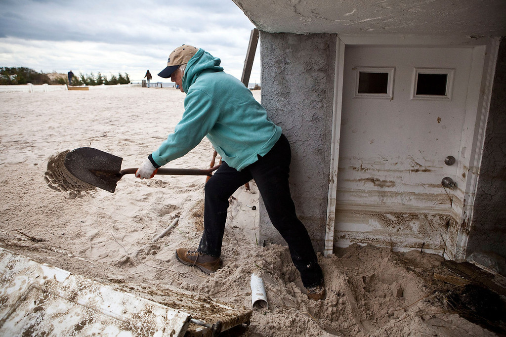 . Barbara Young digs sand out from her front door, which was caused by Hurricane Sandy, on October 31, 2012 in Long Beach, New York.The storm has claimed many lives in the United States and has caused massive flooding across much of the Atlantic seaboard. U.S. President Barack Obama has declared the situation a \'major disaster\' for large areas of the U.S. east coast, including New York City, with widespread power outages and significant flooding in parts of the city.  (Photo by Andrew Burton/Getty Images)