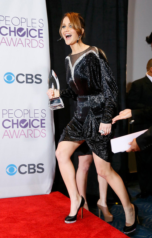 Description of . Jennifer Lawrence arrives backstage with the award for favorite movie actress at the 2013 People's Choice Awards in Los Angeles, January 9, 2013.     REUTERS/Danny Moloshok