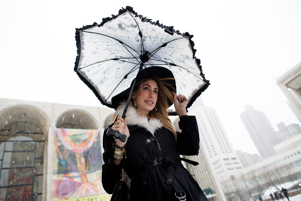 Description of . Lauren Rae Levy, of Manhattan, stands outside the Metropolitan Opera House in the snow at Lincoln Center during Fashion Week, Friday, Feb. 8, 2013, in New York. Snow began falling across the Northeast on Friday, ushering in what was predicted to be a huge, possibly historic blizzard and sending residents scurrying to stock up on food and gas up their cars. (AP Photo/John Minchillo)