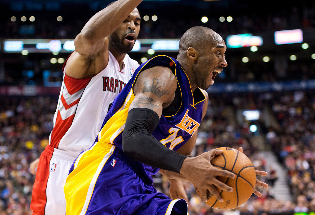 Description of . Los Angeles Lakers guard Kobe Bryant, right, drives the net past Toronto Raptors Alan Anderson, left, during first half NBA basketball action in Toronto on Sunday Jan. 20, 2013. (AP Photo/THE CANADIAN PRESS,Nathan Denette)