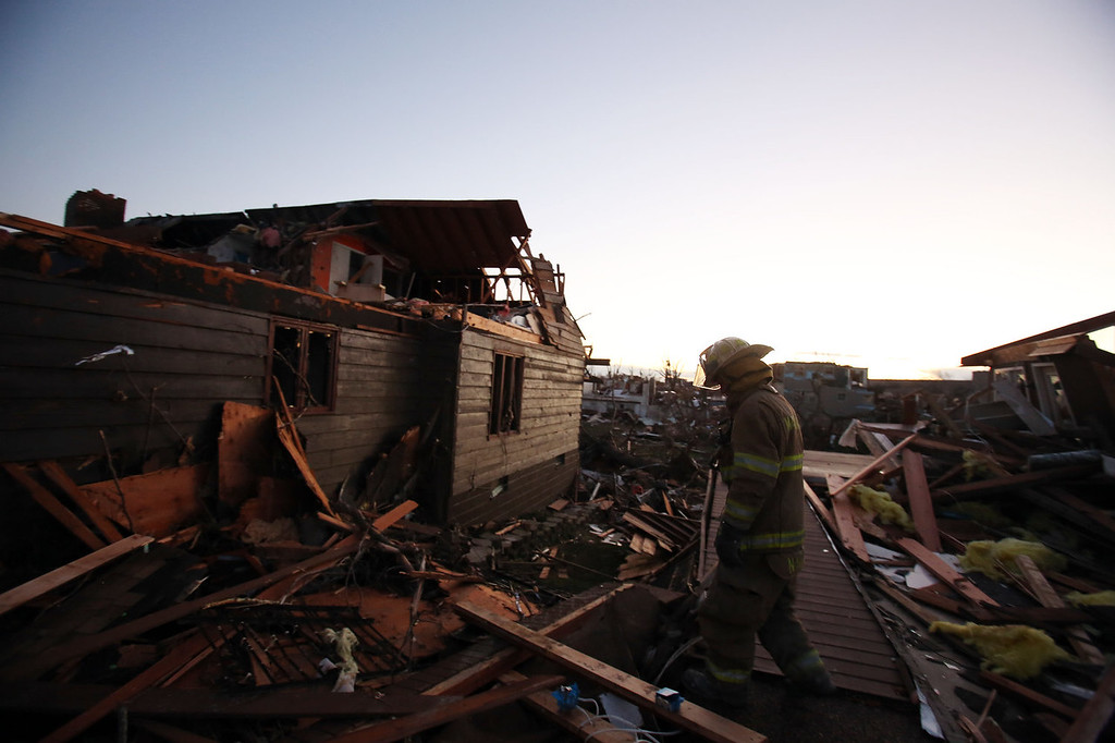 Description of . A firefighter searches through debris after a tornado struck on November 17, 2013 in Washington, Illinois. Several tornadoes touched down across the Midwest today with at least three people reported dead in Illinois. (Photo by Tasos Katopodis/Getty Images)