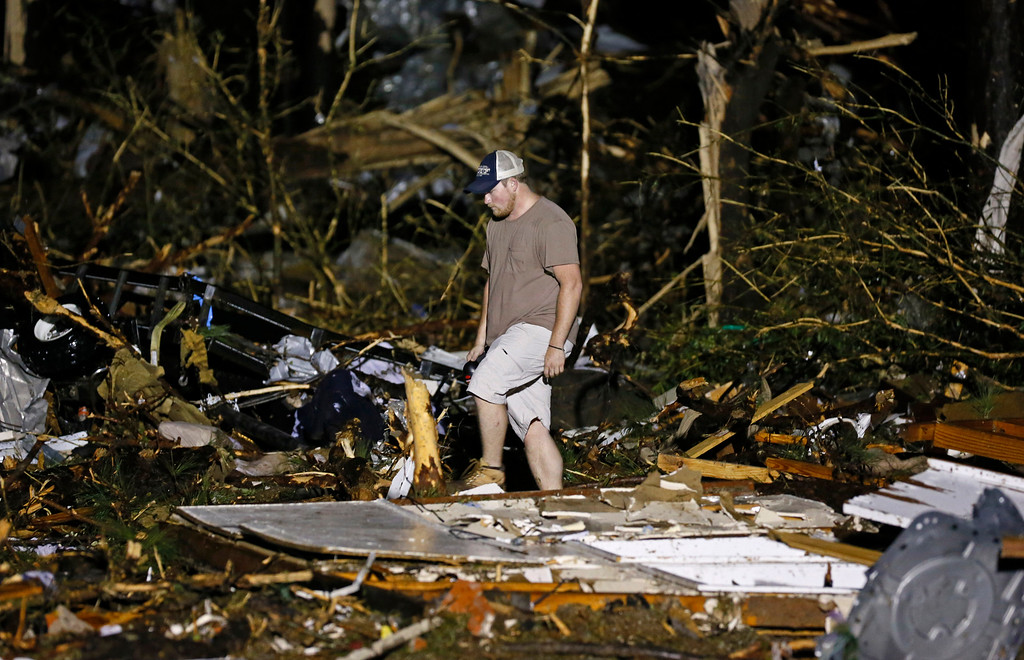 Description of . A volunteer searches the remains of several mobile homes in Louisville, Miss., early Tuesday morning, April 29, 2014 after a tornado hit the east Mississippi community Monday.  (AP Photo/Rogelio V. Solis)