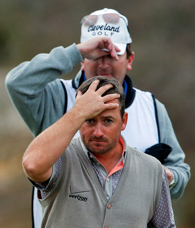 Description of . Northern Ireland\'s Graeme McDowell walks off the course after winning 2 up against Padraig Harrington, of Ireland, in the first round during the Match Play Championship golf tournament, Thursday, Feb. 21, 2013, in Marana, Ariz. (AP Photo/Ross D. Franklin)