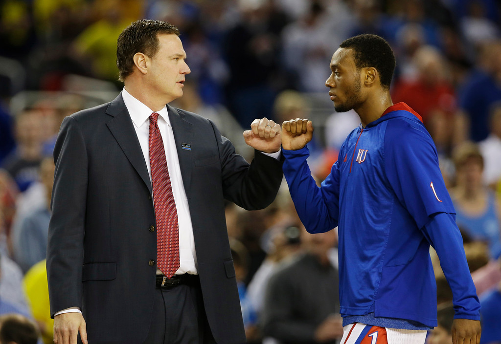 Description of . Kansas head coach Bill Self talks to Naadir Tharpe before a regional semifinal game in the NCAA college basketball tournament, Friday, March 29, 2013, in Arlington, Texas. (AP Photo/Tony Gutierrez)