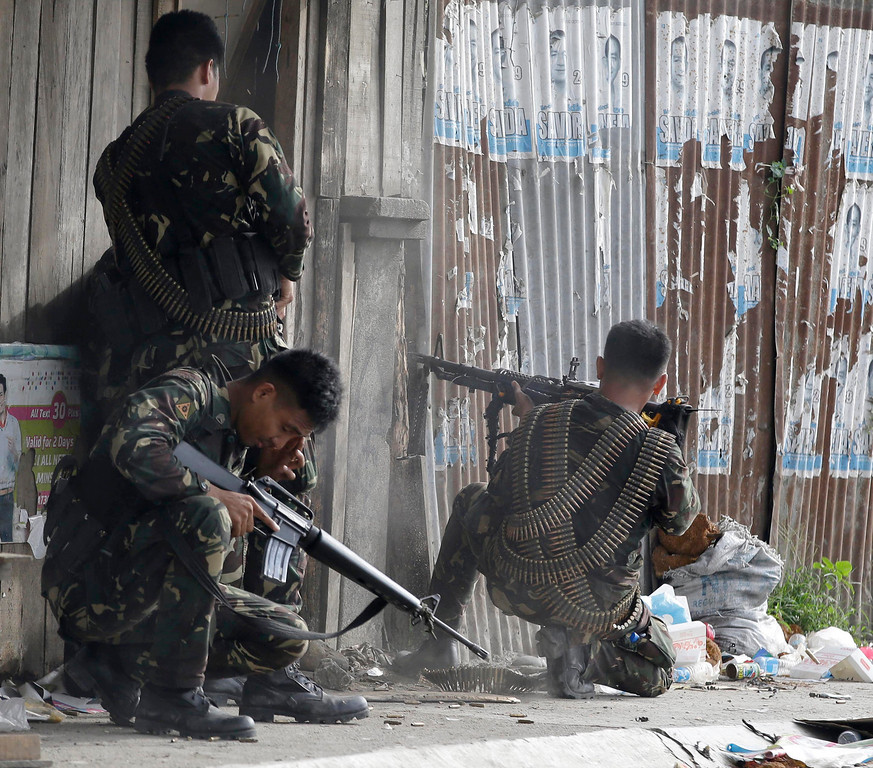 Description of . Government troopers fire their weapons as they continue their assault at Muslim rebels Thursday, Sept. 12, 2013 in Zamboanga city in southern Philippines.  (AP Photo/Bullit Marquez)