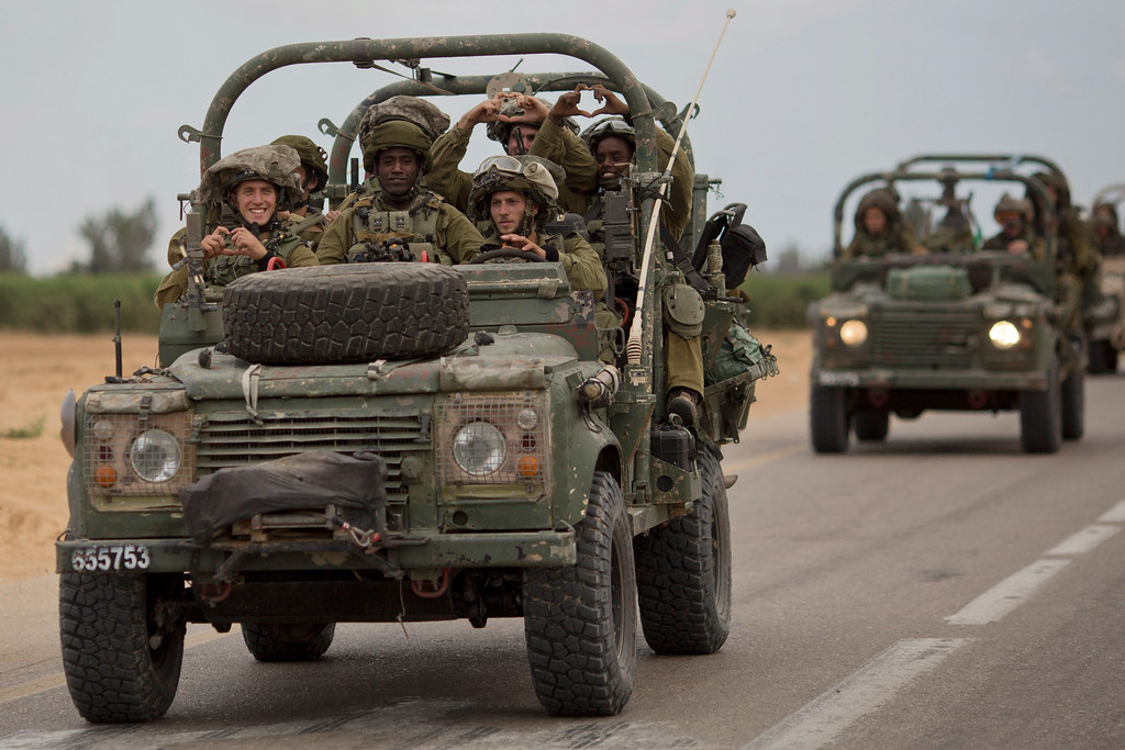 Description of . Israeli soldiers smile as they ride on a military vehicle near the Israel-Gaza Border, Thursday, July 17, 2014. Israel and Hamas have begun observing a five-hour humanitarian cease-fire, as fighting extended into a 10th day. The two sides agreed to the pause following a request by the United Nations so that supplies could be delivered to Gaza.(AP Photo/Ariel Schalit)