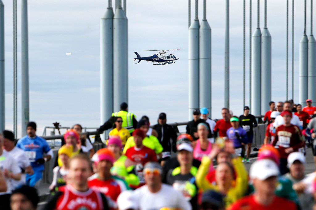 Description of . A police helicopter hovers nearby as runners cross the Verrazano-Narrows Bridge at the start of the New York City Marathon, Sunday, Nov. 3, 2013, in New York. (AP Photo/Jason DeCrow)