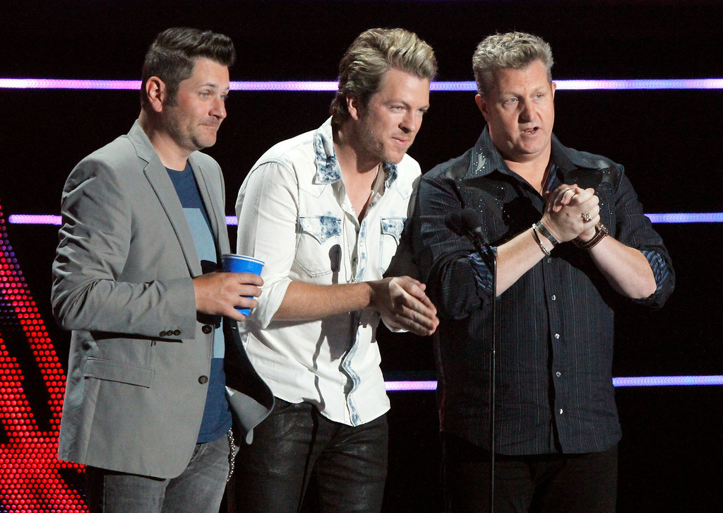 Description of . Jay DeMarcus, from left, Joe Don Rooney and Gary LeVox of the musical group Rascal Flatts present the award for duo video of the year at the CMT Music Awards at Bridgestone Arena on Wednesday, June 4, 2014, in Nashville, Tenn. (Photo by Wade Payne/Invision/AP)