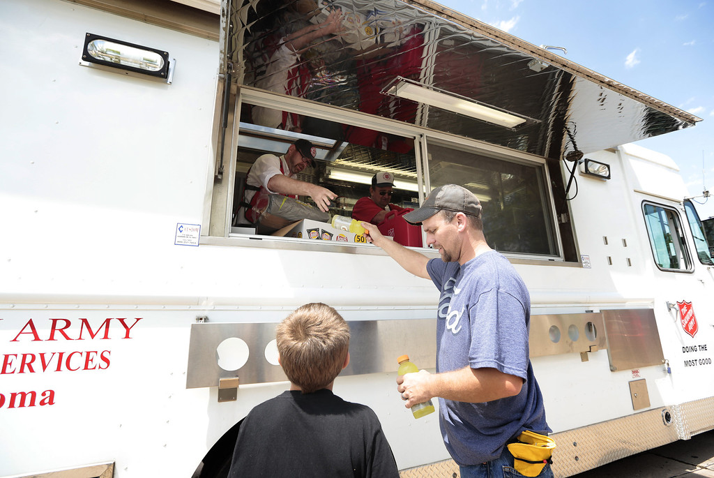 Description of . MOORE, OK -  MAY 23:   Salvation Army Cpt. Jay Spalding hands drinks to Matt Grant and his son Cayden, 8, May 23, 2013  in Moore, Oklahoma. The tornado of at least EF4 strength and up to two miles wide touched down May 20 killing at least 24 people and leaving behind extensive damage to homes and businesses. U.S. President Barack Obama promised federal aid to supplement state and local recovery efforts.    (Photo by Brett Deering/Getty Images)