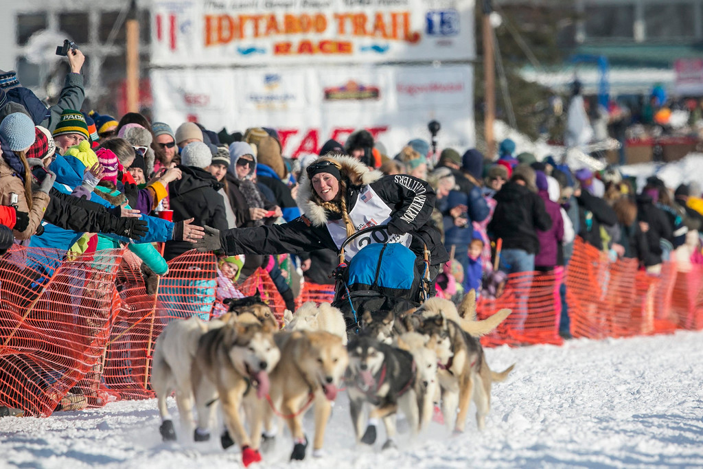 Description of . Kristy Berington greets fans as she heads out of the gate at the re-start of the Iditarod dog sled race in Willow, Alaska March 3, 2013. Berington has a twin who is also racing a team in the Iditarod this year.  REUTERS/Nathaniel Wilder