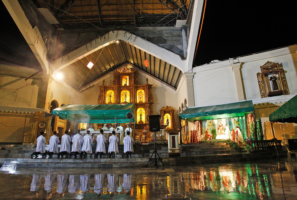 Description of . A preacher pray's during final dawn mass on Christmas eve at Palo Cathedral church in Palo, Leyte province in central Philippine, Wednesday, Dec. 25, 2013. The Christmas eve mass took place in the area devastated by the Nov. 8 typhoon Haiyan's ferocious winds and the tsunami-like storm surge. (AP Photo/Achmad Ibrahim)