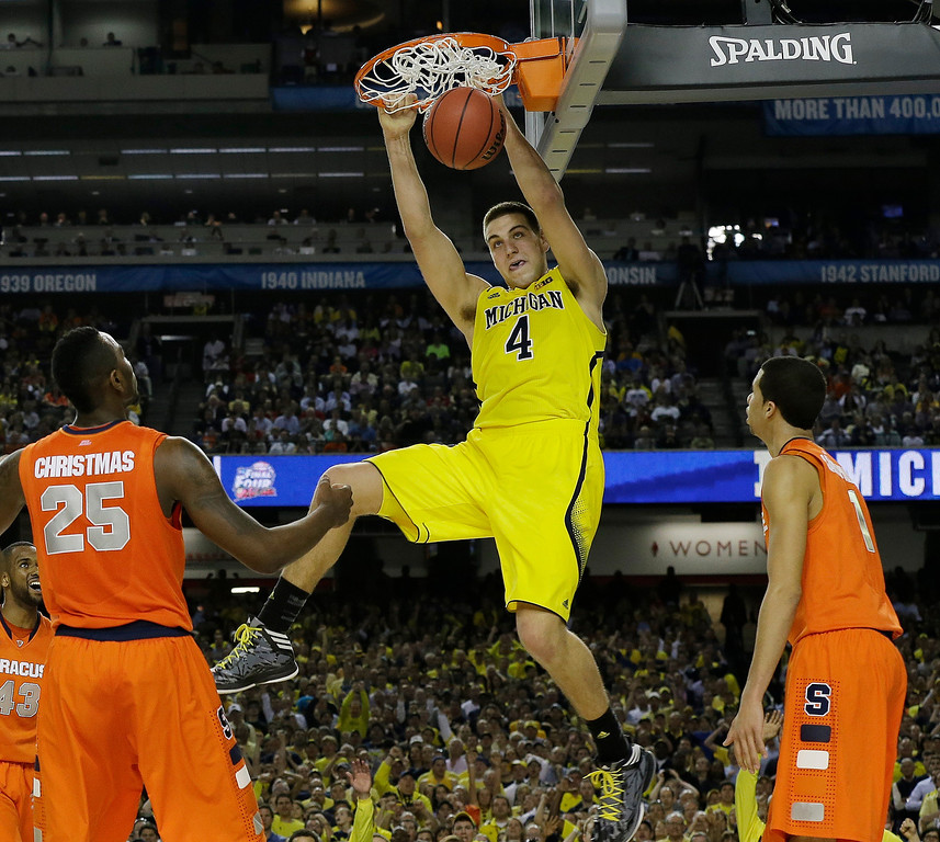 Description of . Michigan's Mitch McGary dunks the ball against Syracuse during the second half of the NCAA Final Four tournament college basketball semifinal game Saturday, April 6, 2013, in Atlanta. (AP Photo/Charlie Neibergall)