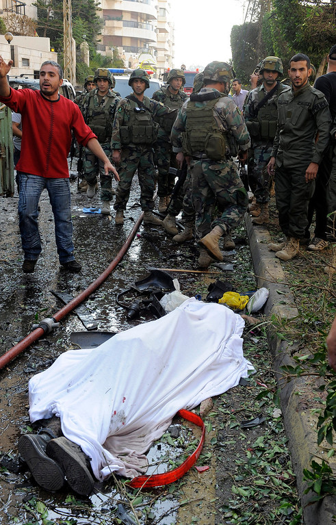 Description of . Lebanese soldiers and civilians gather around a body at the site of explosions near the Iranian embassy in Beirut, Lebanon, 19 November 2013. The death toll from a double suicide bombing near the Iranian embassy in Beirut has risen to 23, including at least two Iranian citizens, the Lebanese Health Ministry says and about 146 others were wounded.  EPA/WAEL HAMZEH