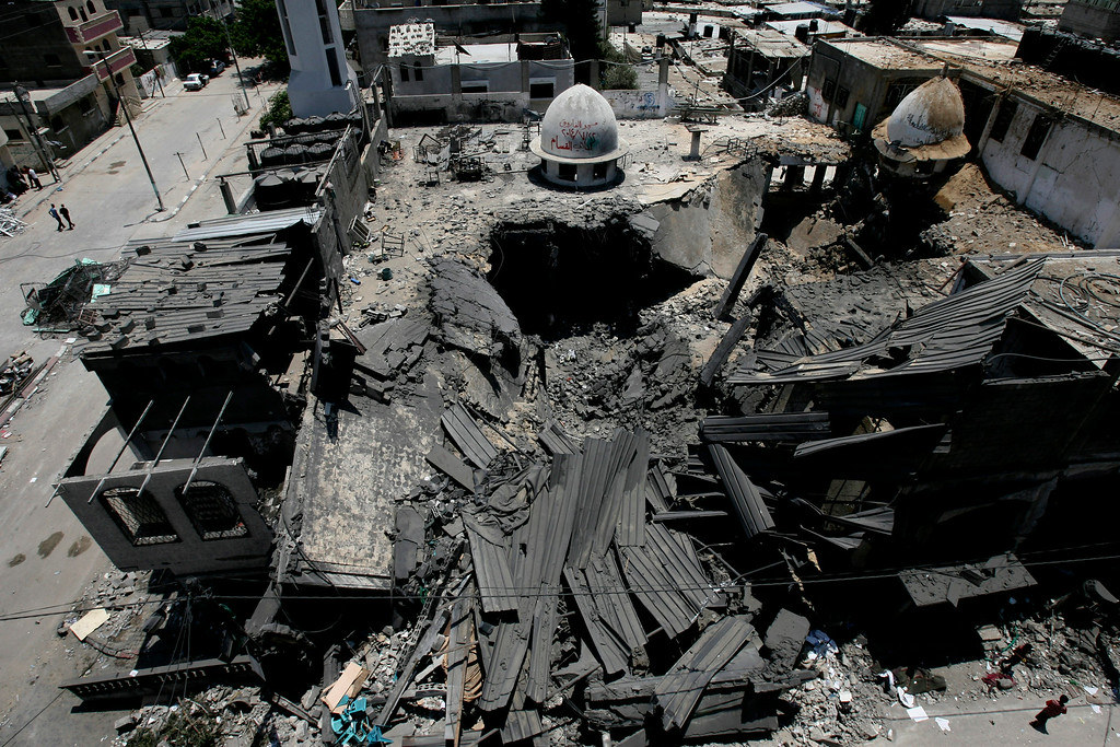Description of . Palestinians inspect Al Farouk mosque destroyed by an overnight Israeli strike, in Rafah, in the southern Gaza Strip, Tuesday, July 22, 2014. Israeli airstrikes pummeled a wide range of locations along the coastal area and diplomatic efforts intensified to end the two-week war that has killed hundreds of Palestinians and dozens of Israelis. (AP Photo/Eyad Baba)
