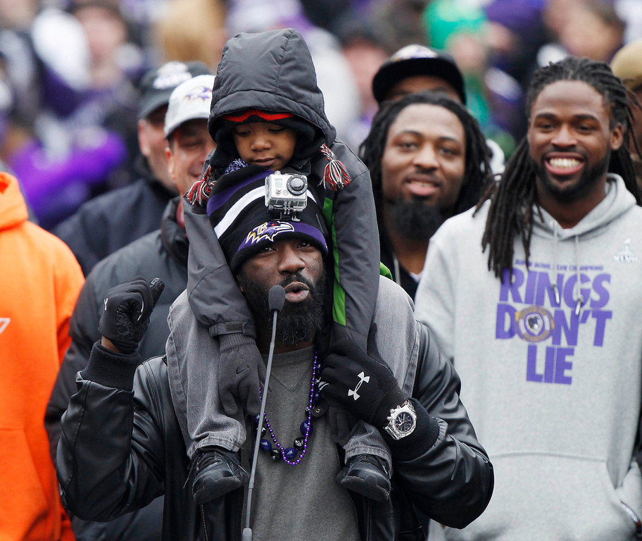 Description of . Super Bowl XLVII champion Baltimore Ravens safety Ed Reed sings to the crowd at a fan and team victory rally in Baltimore February 5, 2013. The Ravens defeated the San Francisco 49ers to win the NFL championship. The child on Reed's shoulders is unidentified.    REUTERS/Gary Cameron