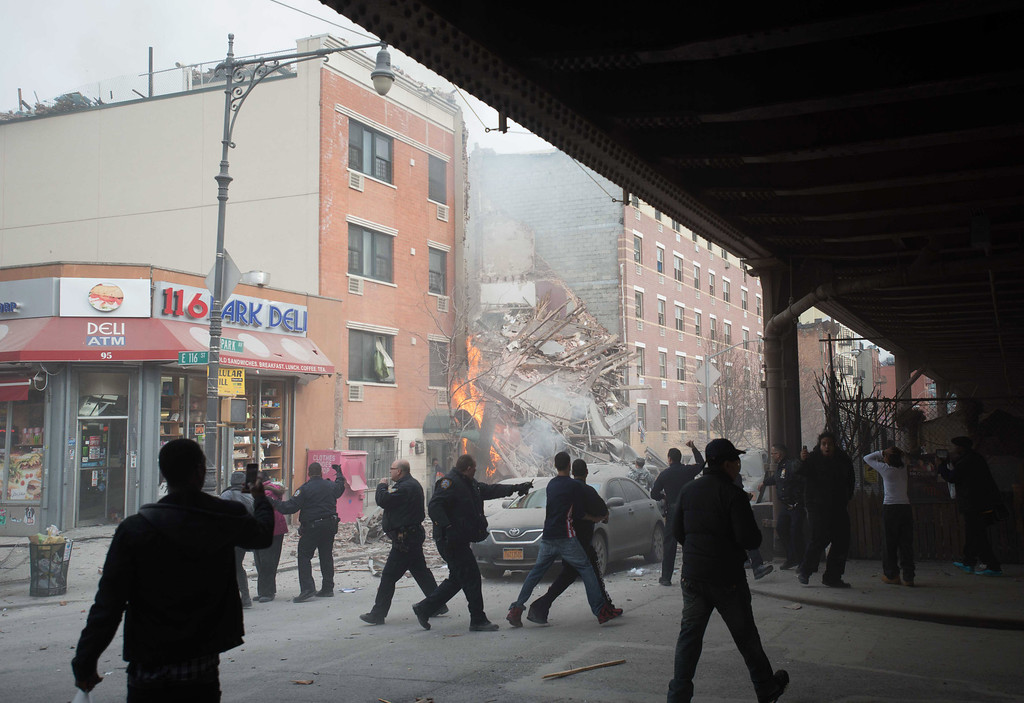 Description of . Police move people away from the scene of an explosion and building collapse in the East Harlem neighborhood of New York, Wednesday, March 12, 2014.  (AP Photo/Jeremy Sailing)