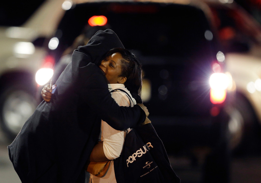 Description of . A woman, right, is reunited with a man in the parking lot of Garden State Plaza Mall following reports of a shooter, Tuesday, Nov. 5, 2013, in Paramus, N.J. Hundreds of law enforcement officers converged on the mall Monday night after witnesses said multiple shots were fired there. (AP Photo/Julio Cortez)