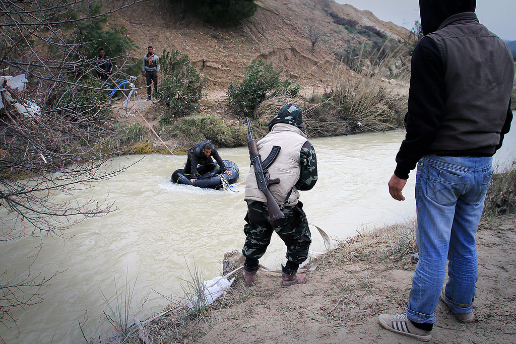 Description of . This photograph taken on February 23, 2012 shows members of the Free Syrian Army moving weapons, medicine and personnel across a river near Al Janoudiyah, in the Idlib province of Syria.  Syrian regime forces killed 11 civilians and wounded 28 others on Monday, after more than 150 people were killed in violence over the weekend, a monitoring group said. The Britain-based monitoring group said explosions shook the Homs neighbourhoods of Hamidiyeh, Bustan al-Diwan, and the city centre. Two others were killed when a rocket fired by regime troops hit a car in which they travelled in the village of Talheya, in the northern province of Idlib, the Observatory said. ENN-Bradley Secker/AFP/Getty Images