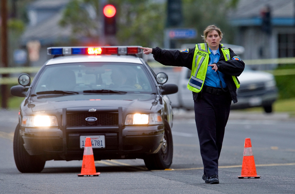 . An Orange police officer directs traffic as an investigation of a shooting continues, Tuesday, Feb. 19, 2013 in Orange County, Calif. (AP Photo/The Orange County Register, Mark Rightmire)