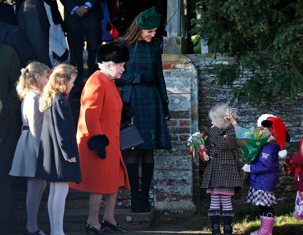 Description of . Britain's Queen Elizabeth II receives flowers from children as the Duchess of Cambridge, top, looks on after members of the royal family attended a Christmas Day Service at St. Mary's church on the grounds of Sandringham Estate, the Queen's royal estate in Norfolk, England, Wednesday, Dec. 25, 2013. (AP Photo/Lefteris Pitarakis)