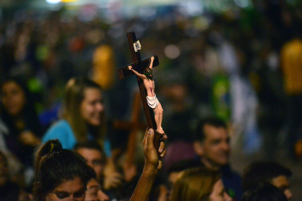 Description of . A Catholic pilgrim attending World Youth Day (WYD) holds a crucifix as he waits for the arrival of Pope Francis for a prayer vigil at Copacabana beach in Rio de Janeiro, Brazil, on July 27, 2013. CHRISTOPHE SIMON/AFP/Getty Images