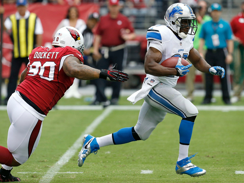 Description of . Detroit Lions running back Reggie Bush escapes the reach of Arizona Cardinals defensive end Darnell Dockett (90) during the first half of a NFL football game, Sunday, Sept. 15, 2013, in Glendale, Ariz. (AP Photo/Ross D. Franklin)