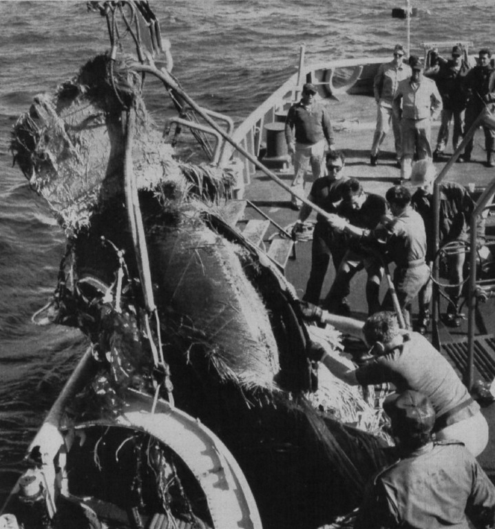 . Crewmen aboard the USS Preserver, a U.S. Navy salvage ship, hoist aboard what is believed to be the remains of the solid rocket propellant cases of the inertial upper stage. The IUS was carried in the cargo of the Challenger.   Denver Post Library Archive