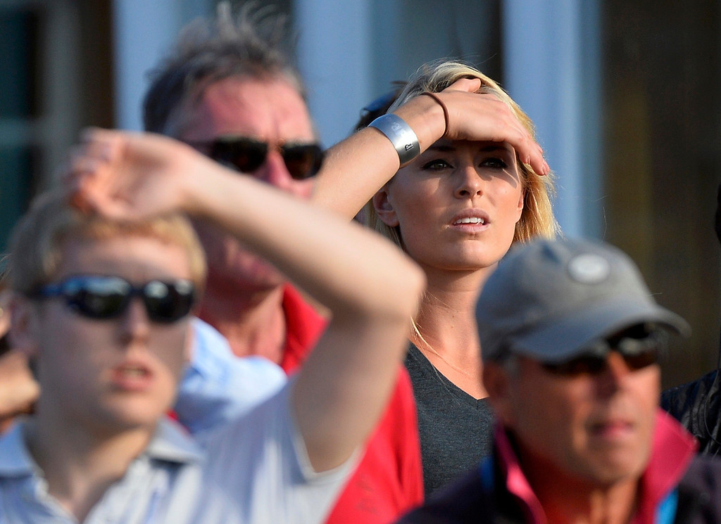 Description of . Skier Lindsey Vonn watches her boyfriend Tiger Woods of the U.S. on the 18th hole, during the third round of the British Open golf Championship at Muirfield in Scotland July 20, 2013.    REUTERS/Toby Melville
