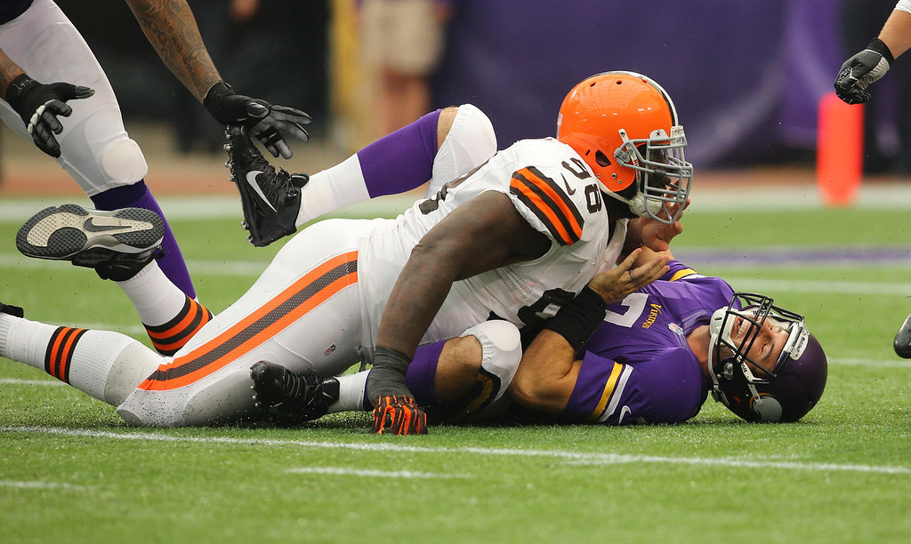 Description of . Christian Ponder #7 of the Minnesota Vikings reacts to a tackle by Phillip Taylor #98 of the Cleveland Browns on September 22, 2013 at Mall of America Field at the Hubert Humphrey Metrodome in Minneapolis, Minnesota. (Photo by Adam Bettcher/Getty Images)