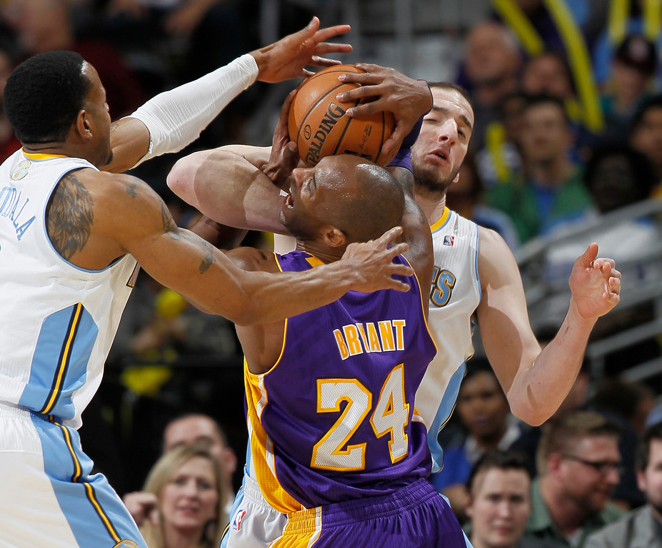 Description of . Los Angeles Lakers guard Kobe Bryant, front right, is fouled while driving for a shot by Denver Nuggets center Kosta Koufos, back right, as guard Andre Iguodala comes in to cover in the third quarter of the Nuggets' 119-108 victory in an NBA basketball game in Denver on Monday, Feb. 25, 2013. (AP Photo/David Zalubowski)
