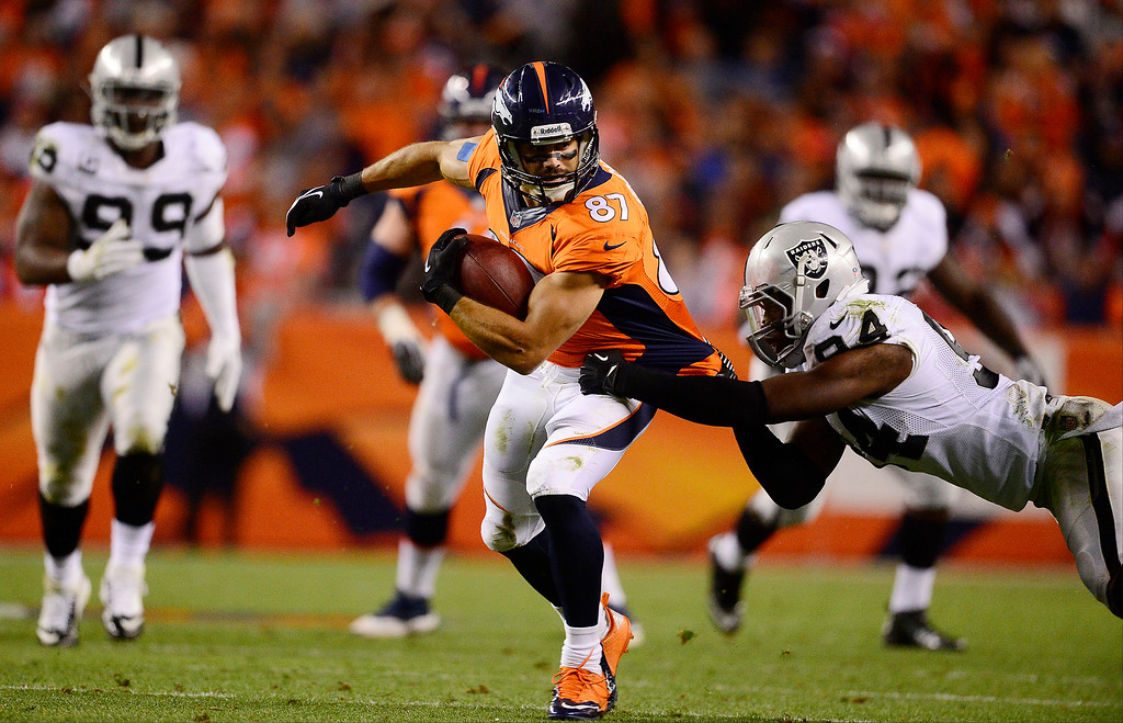 Description of . Denver Broncos wide receiver Eric Decker (87) breaks a tackle in the second quarter. The Denver Broncos took on the Oakland Raiders at Sports Authority Field at Mile High in Denver on September 23, 2013. (Photo by AAron Ontiveroz/The Denver Post)