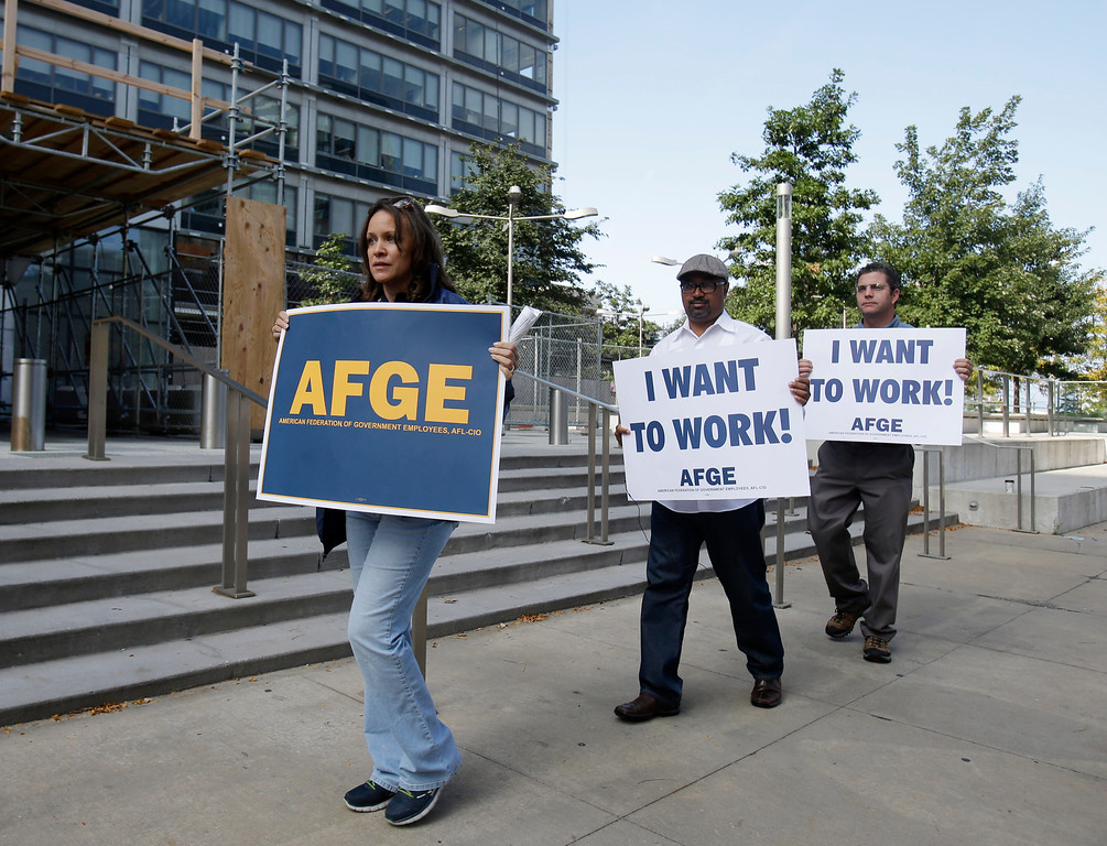 Description of . Darlene Tinsley, left, secretary/treasurer for the American Federation of Government Employees, leads protesters of the government shutdown in front of the Anthony J. Celebreezze Federal Building Tuesday, Oct. 1, 2013, in Cleveland. (AP Photo/Tony Dejak)