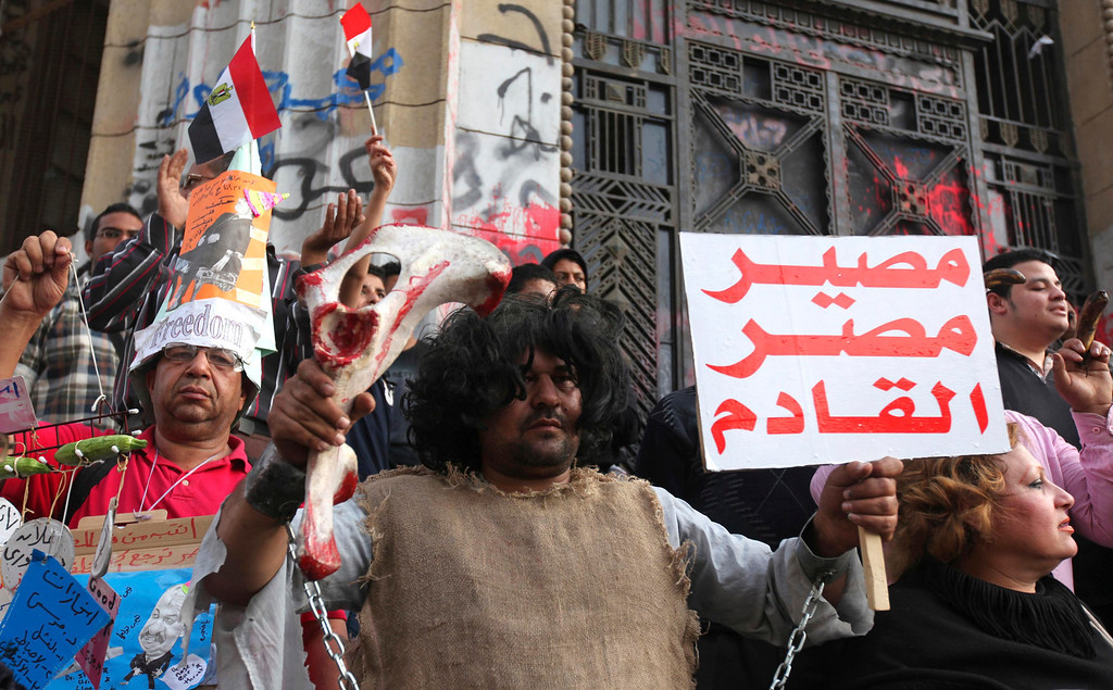 Description of . An activist, dressed as a chained prehistoric man, stands with anti-Mursi demonstrators and members of the 6th of April activist movement in front of the High Court during a rally in Cairo April 6, 2013. The movement calls for a 'Day of Rage' to protest against the arrest of activists and the stifling of free expression. The movement was one of the key players in the uprising that toppled former President Hosni Mubarak. The banner reads,