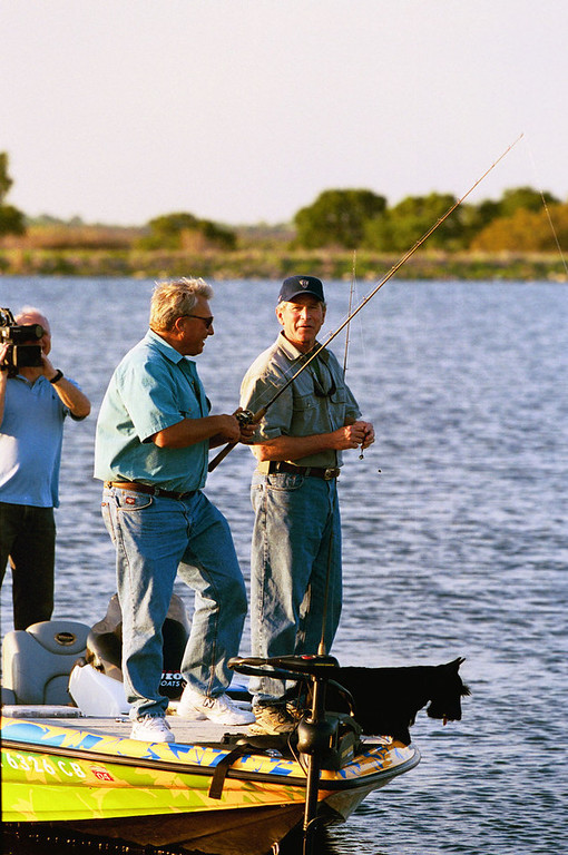 Description of . President Bush appears with with Roland Martin on Martin's fishing show for the Outdoor Life Network, in this April 2004 photo. The episode, taped at a lake on the president's Crawford, Texas ranch, aired  Aug.  6, 2004. Bush's dog, Barney, lower right, also made an cameo appearance. (AP Photo/White House via Outdoor Life Network, Eric Draper)