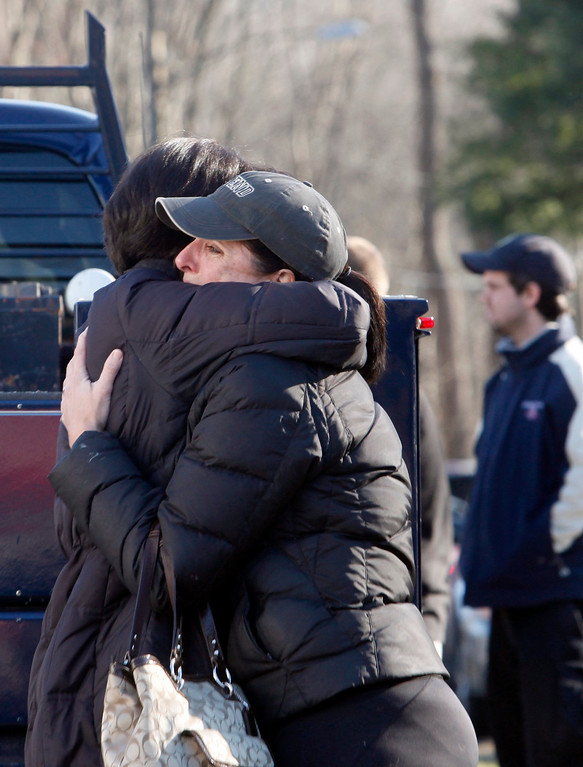 Description of . Relatives embrace each other outside Sandy Hook Elementary School following a shooting in Newtown, Connecticut, December 14, 2012. At least 27 people, including 18 children, were killed on Friday when at least one shooter opened fire at an elementary school in Newtown, Connecticut, CBS News reported, citing unnamed officials.  REUTERS/Michelle McLoughlin