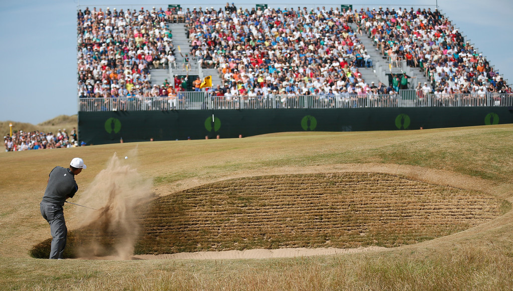 Description of . Tiger Woods of the United States plays a shot out of the bunker on the 4th hole during the third round of the British Open Golf Championship at Muirfield, Scotland, Saturday July 20, 2013. (AP Photo/Peter Morrison)