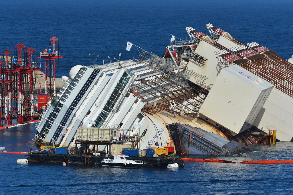 Description of . ISOLA DEL GIGLIO, ITALY - SEPTEMBER 16:  Caissons attached to the side of the stricken Costa Concordia and the cabling used to pull the ship upright are seen as the parbuckling project to raise the ship continues on September 16, 2013 in Isola del Giglio, Italy. Work begins today to right the stricken Costa Concordia vessel, which sank on January 12, 2012. If the operation is successful, it will then be towed away and scrapped. The procedure, known as parbuckling, has never been carried out on a vessel as large as Costa Concordia before. (Photo by Laura Lezza/Getty Images)