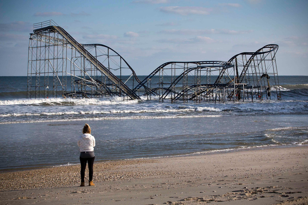 Description of . A woman looks at a roller coaster sitting in the ocean, when the boardwalk it was built upon collapsed during Hurricane Sandy, in Seaside Heights, New Jersey November 28, 2012. The storm made landfall along the New Jersey coastline on October 29, 2012 - one month ago tomorrow. REUTERS/Andrew Burton