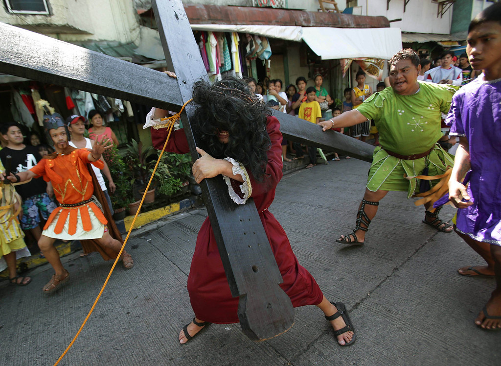Description of . A man portraying Jesus Christ grimaces as he carries a cross during a reenactment of Christ's suffering and death as part of Maundy Thursday rituals to atone for sins on March 28, 2013 in suburban Mandaluyong, east of Manila, Philippines. The ritual is frowned upon by church leaders in this predominantly Roman Catholic country.  (AP Photo/Aaron Favila)