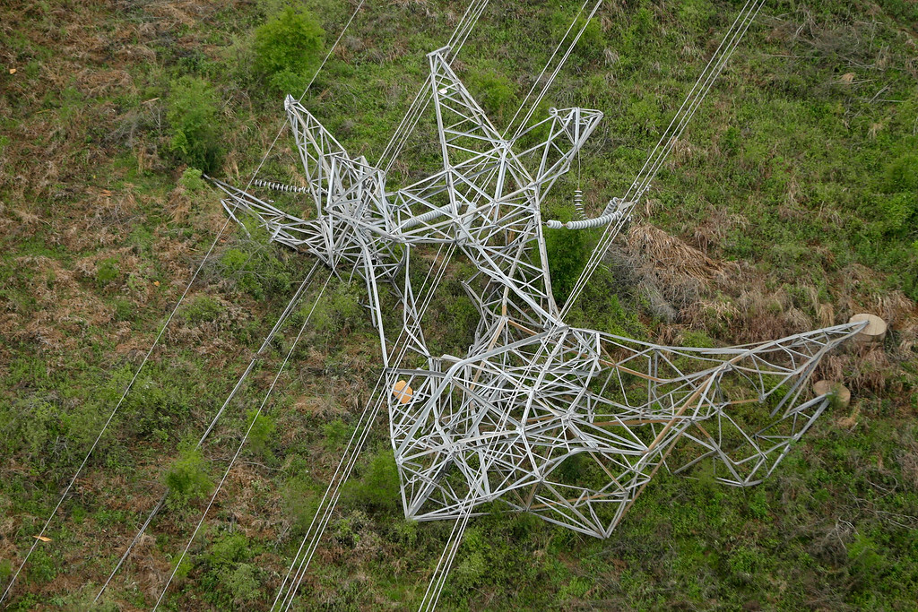 Description of . A twisted power distribution line tower is crumpled on the ground near Mayflower, Ark., Monday, April 28, 2014 after a tornado struck the town late Sunday.   (AP Photo/Danny Johnston)